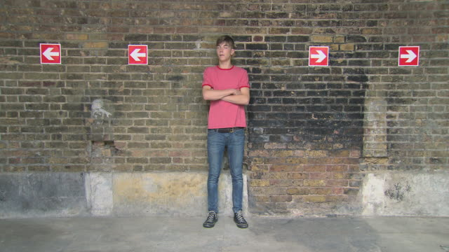 Teenage boy looking at arrows on wall then walking off