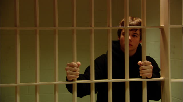Ms Teenage Boy Looking Worried As He Grips Bars In Prison Cell New ...