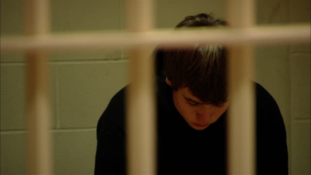 ms teenage boy looking worried as he sits in prison cell/ new jersey - prisoner stock videos & royalty-free footage