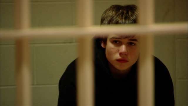 ms teenage boy looking worried as he sits in prison cell/ new jersey - crime stock videos & royalty-free footage