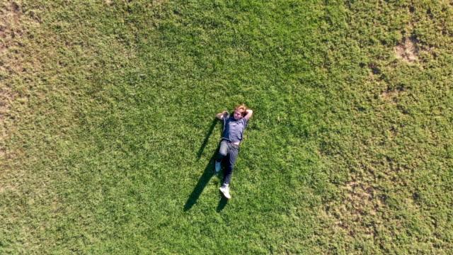 vidéos et rushes de adolescent se trouvant sur l'herbe utilisant son téléphone intelligent - personne sereine