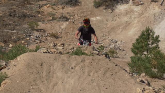 Teenage boy mountain biker doing tricks off dirt jumps. - Slow Motion
