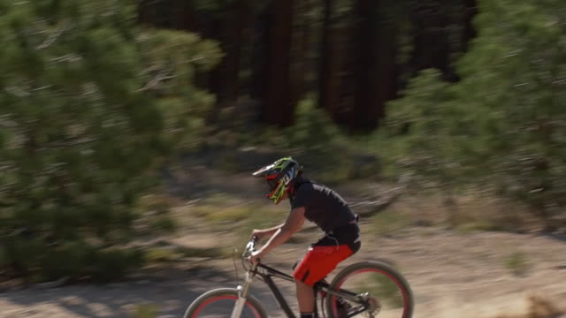 teenage boy mountain biker doing tricks off dirt jumps. - slow motion - dirt track stock videos & royalty-free footage