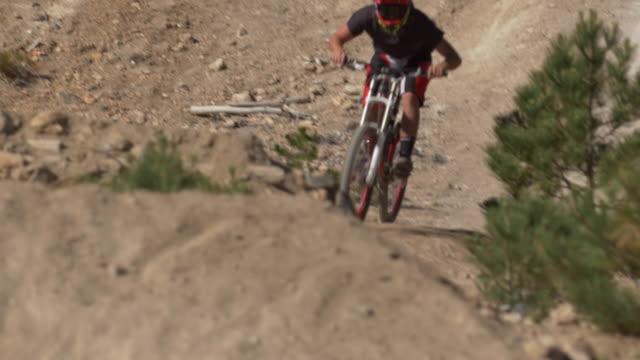 teenage boy mountain biker doing tricks off dirt jumps. - mountain biking stock videos & royalty-free footage