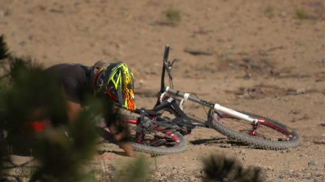 Teenage boy mountain biker laying on the ground after crashing. - Slow Motion