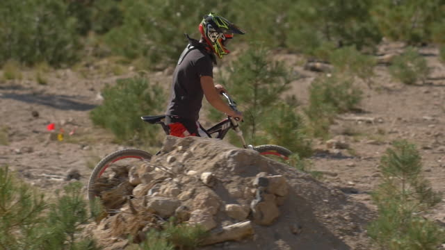 teenage boy mountain biker walking with bike to top of trail. - slow motion - one teenage boy only stock videos & royalty-free footage