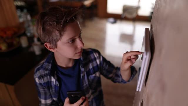スマートホームシステムとスマートフォンをペアリングする10代の少年 - エアコン点の映像素材/bロール