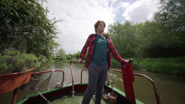 a teenage boy piloting a narrow boat along the river stort - part of a series stock-videos und b-roll-filmmaterial