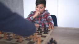 Teenage boy playing chess with his brother