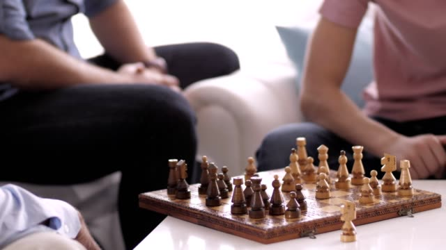 stockvideo's en b-roll-footage met teenage boy spelen schaken met zijn grootvader - spelletjesavond