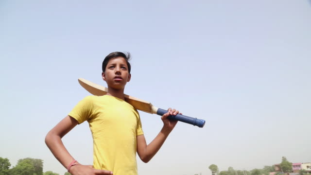Teenage boy playing cricket, Haryana, India