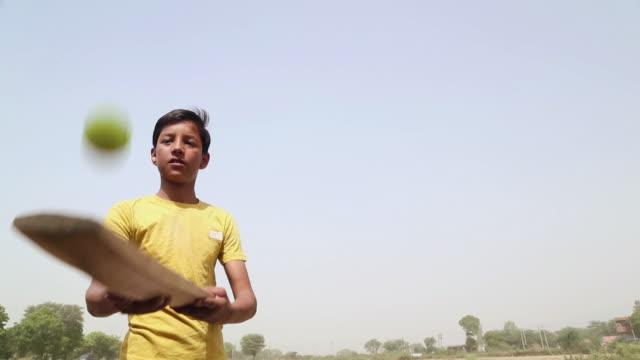 Teenage boy playing cricket, Haryana, India