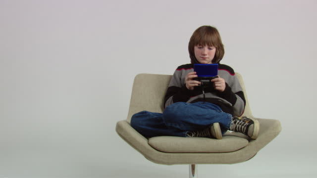 ws teenage boy playing handheld video game and sitting in chair / new york, usa - handheld video game stock videos & royalty-free footage