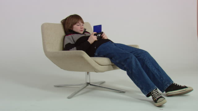 WS Teenage boy playing handheld video game and slouching in chair / New York, USA