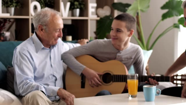 teenage boy playing the guitar for his family - grandfather stock videos & royalty-free footage