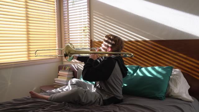 ms teenage boy playing trombone at home - trombone stock videos & royalty-free footage