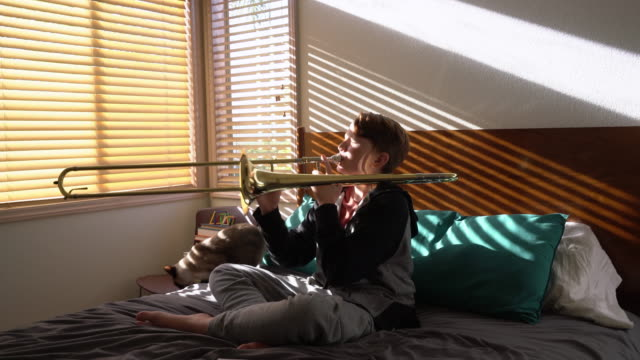 ms teenage boy playing trombone in his bedroom - one teenage boy only stock videos and b-roll footage