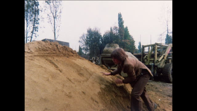 montage teenage boy playing with cement mixer and pile of sand at construction site / united kingdom - one teenage boy only stock videos & royalty-free footage