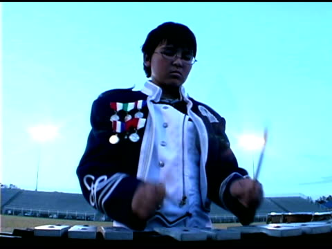 vídeos de stock e filmes b-roll de teenage boy playing xylophone in marching band - banda de marcha