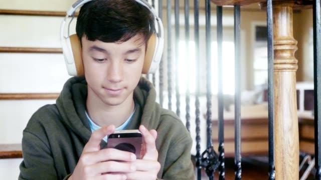 stockvideo's en b-roll-footage met de tiener speelt mobiel spel op smartphone - tienerjongens