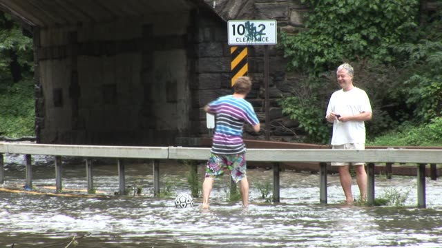 teenage boy plays with soccer ball in flood waters. zoom out to reveal area bronx river parkway flooded on august 28, 2011 in scarsdale, new york - hurricane irene stock videos & royalty-free footage