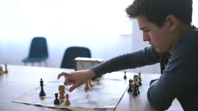 Teenage boy practicing chess alone