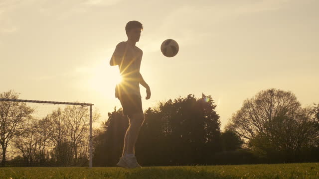 stockvideo's en b-roll-footage met teenage boy practising football skills - schoppen lichaamsbeweging