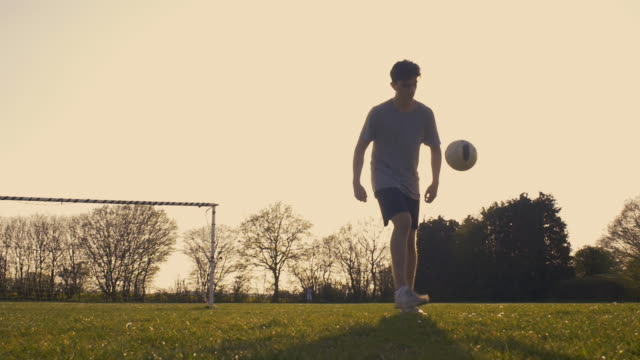 teenage boy practising football skills - grass family stock videos & royalty-free footage