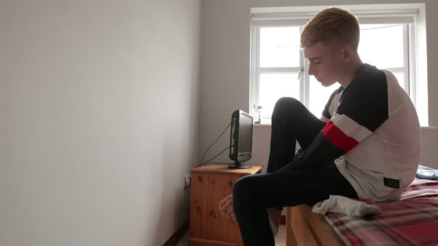 Teenage Boy Putting on Socks