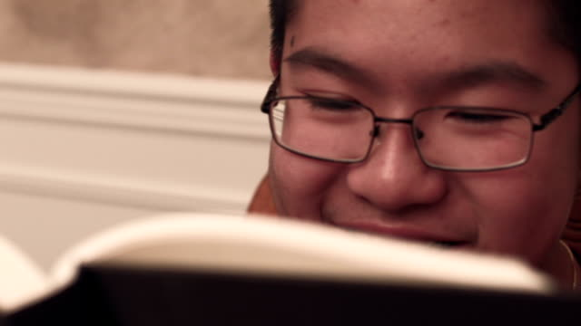 teenage boy reading a book at home - one teenage boy only stock videos & royalty-free footage