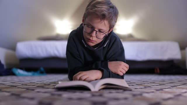 vidéos et rushes de adolescent affichant un livre sur l'étage - un seul petit garçon