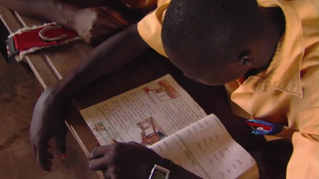 CU HA Teenage boy reading aloud sitting in classroom, Tamale, Ghana