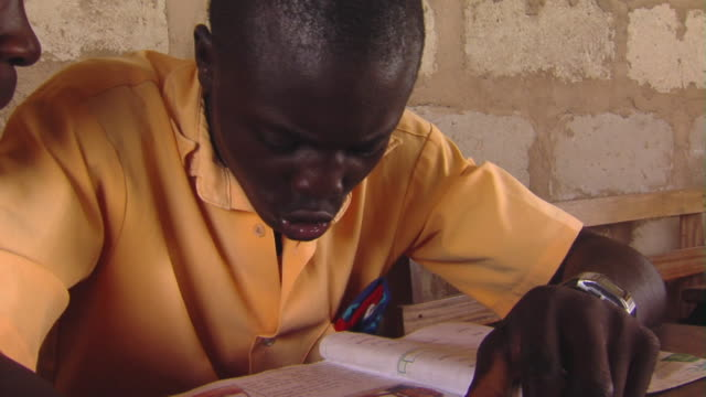 cu teenage boy reading in classroom, tamale, ghana - one teenage boy only stock videos & royalty-free footage