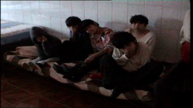 vídeos y material grabado en eventos de stock de teenage boy rescued from romanian orphanage as a child visits his country romania int romanian orphan boys seated on a bed rocking backwards and... - orfanato
