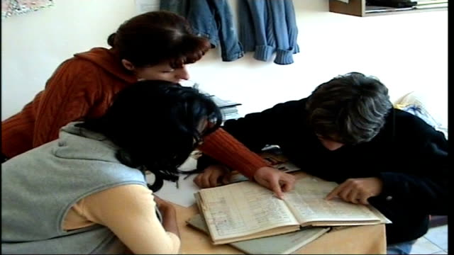 vidéos et rushes de teenage boy rescued from romanian orphanage as a child visits his country; petrauscu looking at handwritten records of orphans kept in the orphanage... - orphelinat