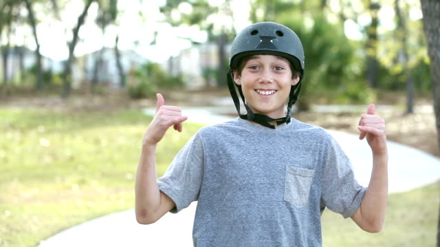 Teenage boy rides skateboard in park toward camera