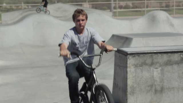 Teenage boy riding BMX bike in a skate park