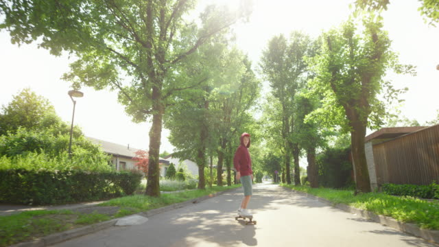 slo mo ts teenage boy riding his skateboard down the sunny street - teenage boys stock videos & royalty-free footage