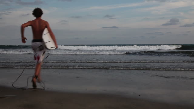 teenage boy running into ocean with his surfboard - one teenage boy only stock videos & royalty-free footage