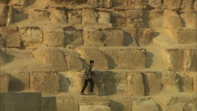 MS, ZO, TU Teenage boy (14-17)  running on Giza Pyramid, Giza Plateau / Giza, Egypt