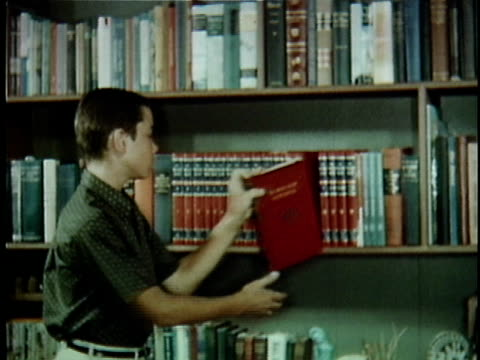 vídeos de stock, filmes e b-roll de montage ms teenage boy selecting encyclopedia from library shelf / cu boy reading book in library / knights ferry, california, usa - esetante de livro