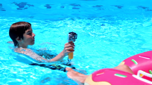 teenager, die video-aufnahmen im schwimmbad, handheld erschossen - schwimmflügel stock-videos und b-roll-filmmaterial