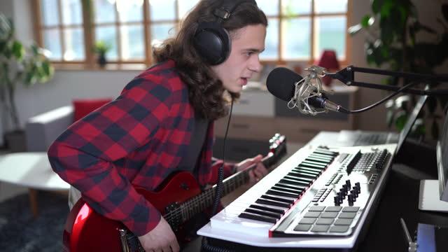 vidéos et rushes de adolescent chantant et faisant la musique au studio d'enregistrement à la maison - singer