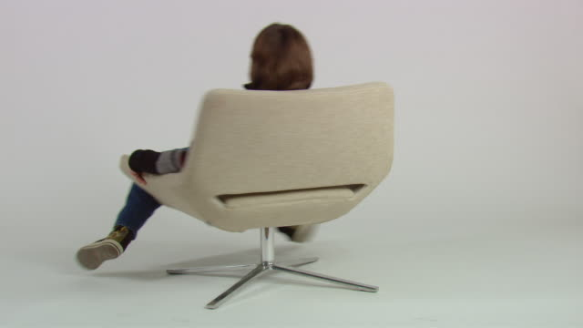 ws teenage boy sitting and spinning in chair / new york, usa - one teenage boy only stock videos and b-roll footage
