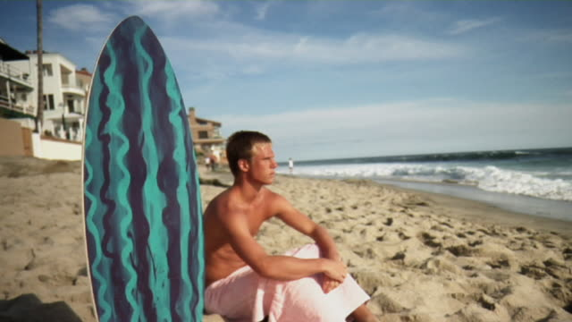 ms teenage boy sitting by surfboard on beach, laguna beach, california usa - one teenage boy only stock videos & royalty-free footage