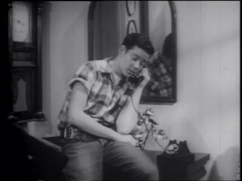 b/w 1953 teenage boy sitting on edge of furniture talking on telephone - one teenage boy only stock videos & royalty-free footage