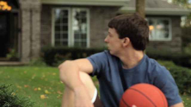 vídeos de stock, filmes e b-roll de ms r/f teenage boy (16-17) sitting on lawn holding basketball / neenah, wisconsin, usa  - esporte de equipe