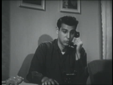 b/w 1951 teenage boy sitting + talking on telephone - 1951年点の映像素材/bロール
