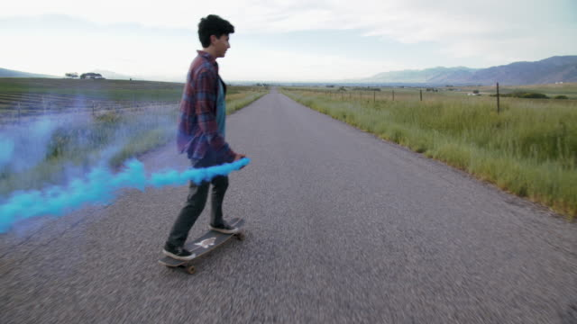 ws teenage boy skateboarding down a road - youth culture stock videos & royalty-free footage