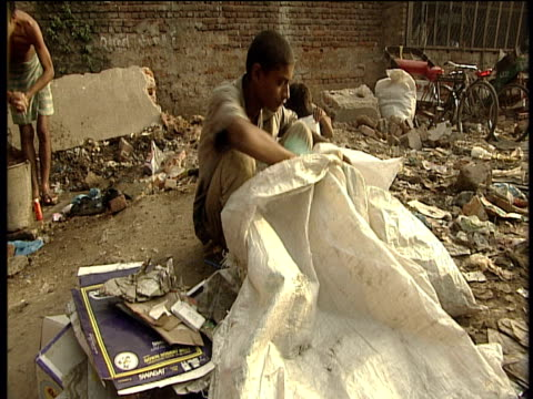 Teenage boy sorts through pile of rubbish and collects waste paper in sack New Delhi